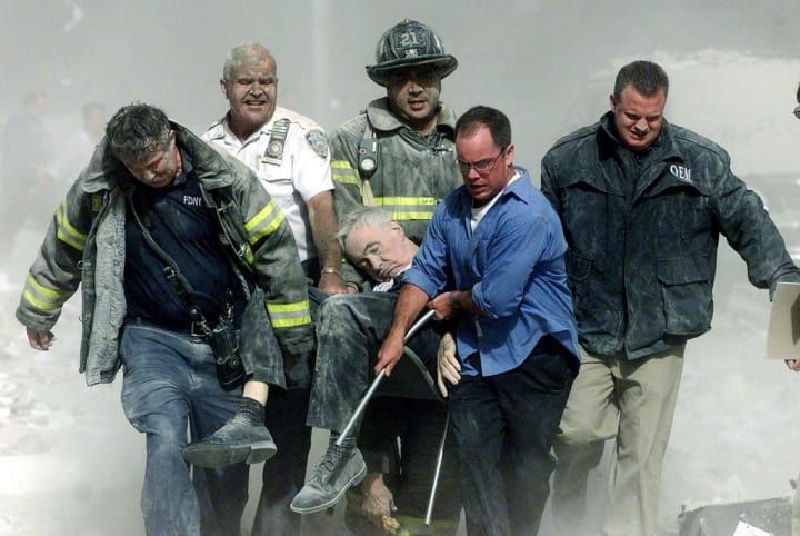 In this picture, rescue workers carry fatally injured New York City Fire Department Chaplain Mychal Judge from one of the World Trade Center towers. That morning, Judge rushed to the site to pray over the dead and wounded in the streets. When the south tower collapsed, Father Judge was killed after being struck in the head by falling debris. According to Judge's biographer, at the time of his death he was praying aloud, 'Jesus, please end this right now! God, please end this!'