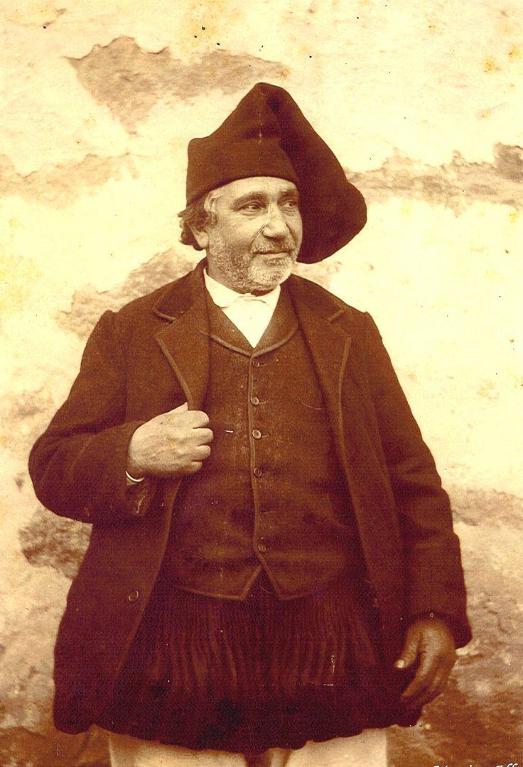 Ales, Sardegna, Italy ~ L'abbigliamento maschile era costituito da un copricapo in panno nero, una camicia bianca, un corpetto (gilet) nero, ed una giacca in velluto nero. I pantaloni bianchi, venivano coperti da una sorta di gonnellino nero detto su crazzoni de arroda.Questo tipo di abbigliamento detto su complettu; utilizzato sia d'estate che d'inverno; nelle stagioni invernali si indossava un cappotto di orbace con cappuccio. A completare l'abbigliamento gli stivali a gambaletto.