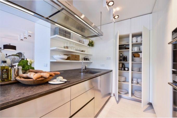 Nerezový modul kuchyně Varena s digestoří a pracovní deskou z flambované žuly doplňují bílé karvrované skříňky (jakoby krájený deskovitě členěný povrch). Kuchyň je vybavena spotřebiči Siemens