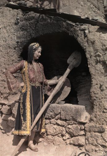An actress in costume of Epirus stands at an outdoor oven. Location: Mount Parnassus, Greece.  Photographer: MAYNARD OWEN WILLIAMS/National Geographic Creative