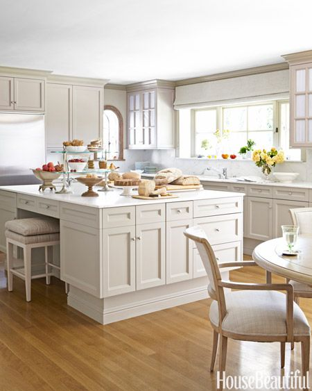 """The kitchen was bright white, but because it got constant light from the garden, Barry mellowed it with """"a shadowy color, one you can't quite describe — mushroomy, taupey, tree-barky. I love colors you can't describe,"""" she says. """"It instantly made the room warmer and more intimate. In fact, it feels more like a room than a kitchen."""" Cabinets are painted Farrow & Ball's Light Gray. Walls are covered in a strié paper, Drag, also by Farrow & Ball. Conrad window shade."""