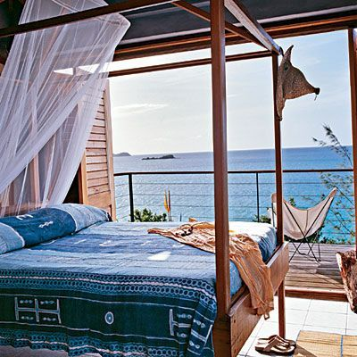 Bedroom open to water front | lounge chair on balcony | indoor outdoor living