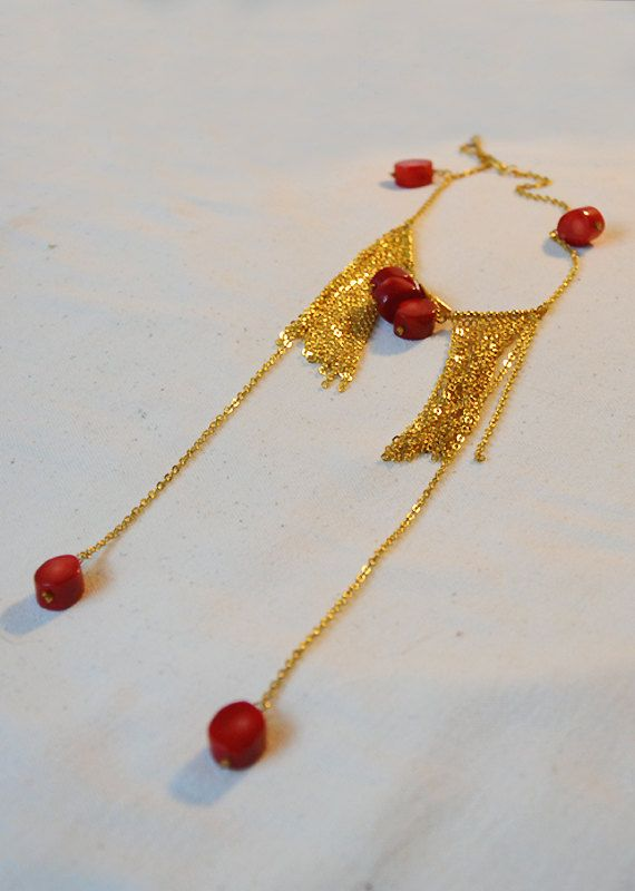SOLD A gold plated fringe necklace with red oval bead corals, 22K gold plated mini spike charms and a lobster clasp closure! Beautiful and elegant! The golden fringe of the chains give it a unique look! Is it yours?!... It is wrapped in a beautiful gift box and can be send to you or to whomever you like in 1-2 business days! Convo me for any questions you may have! NOTE: as all gold plated items,keep your necklace away from perfume!
