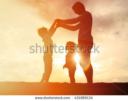 father and two kids playing on sunset sky