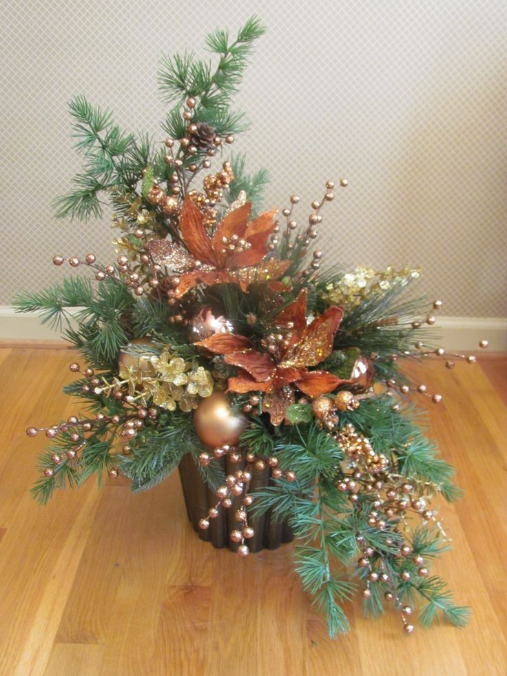One of a reverse matched pair of artificial Christmas arrangements in a bronze bamboo cachepot of mixed metalics (gold, bronze, and copper)- a variety of mixed pine greens, glass balls, eucalyptus, pine cones, poinsettias, and berries.
