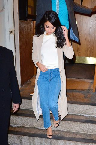 62 fashionable ways to style denim: Selena Gomez styles her blue jeans with a white turtleneck and duster jacket