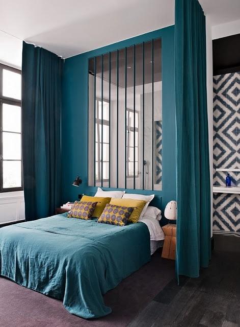 Chambre majestueuse avec ses immenses rideaux bleu canard ; belle harmonie de couleurs, papier graphique aux murs. Et la verrière qui sépare la chambre de la salle de bain, toute en hauteur,  est vraiment très élégante.