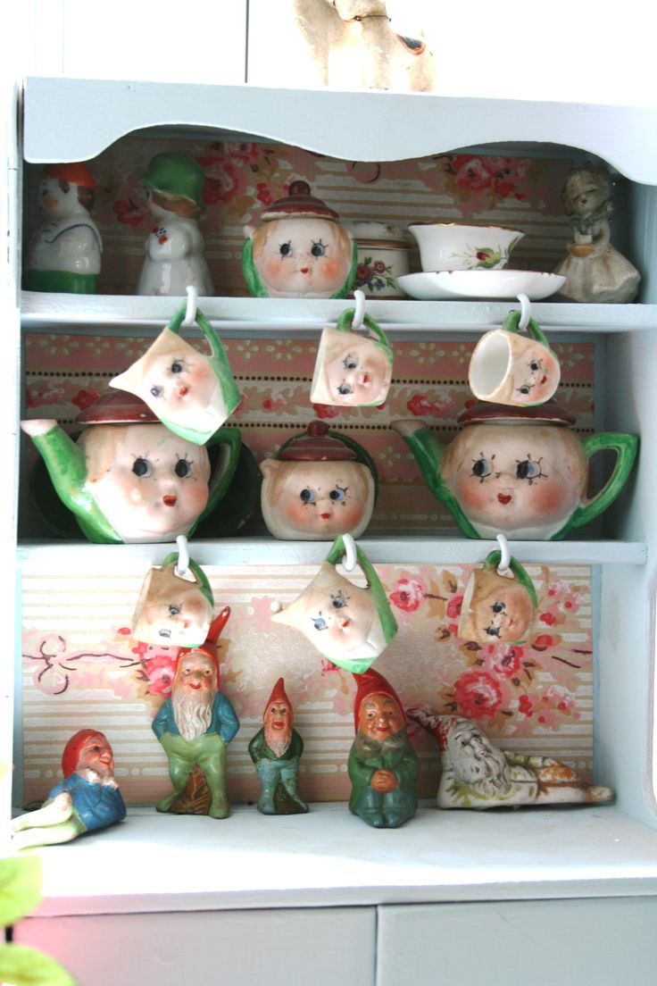Cute kitchen cupboard with teapots and cups with faces
