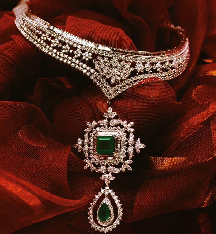 A lotus necklace elegantly holding together a stunning ensemble of pave, prong and channel set diamonds with a princess cut emerald center, baguette diamonds and a gorgeous emerald droplet.