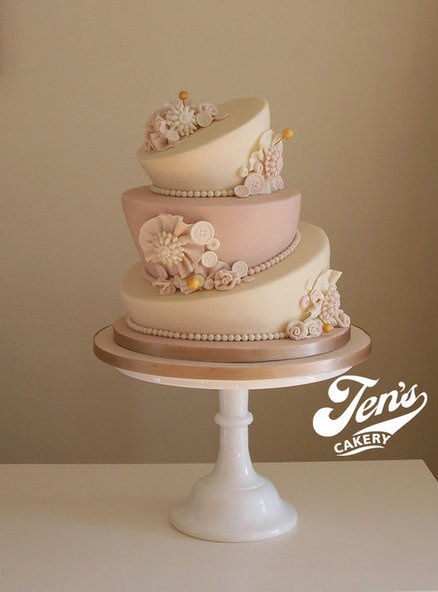 A very classy pink and beige topsy-turvy wedding cake with sugar flowers.   Something a little different