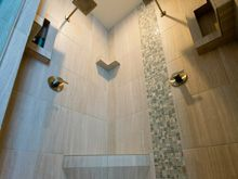 this shower started with a custom shower pan before tiling white matter shelves and
