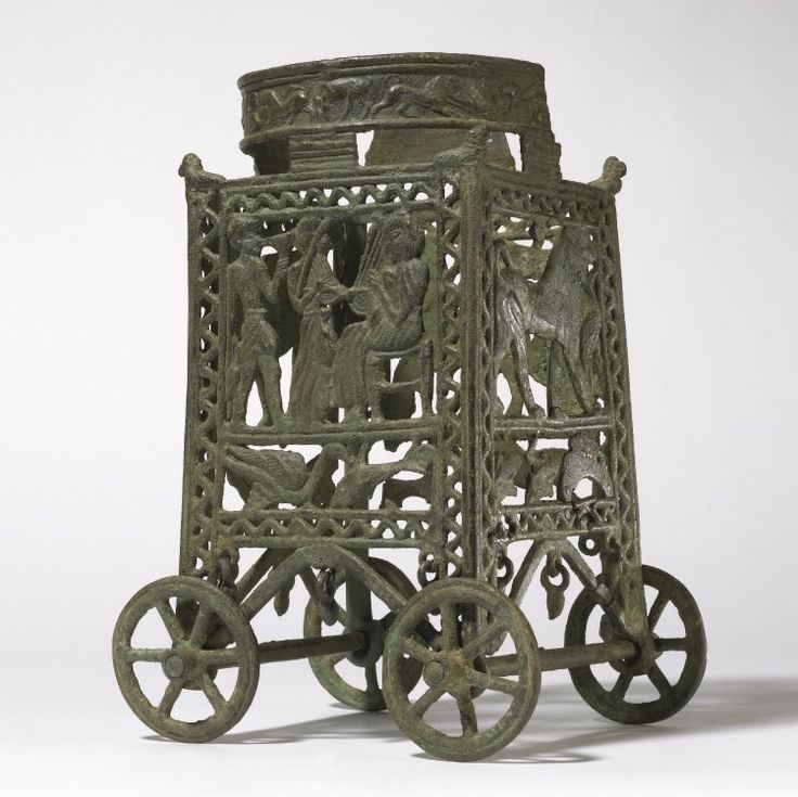 Cypriot bronze wheeled stand for a vessel,  1250 B.C.-1100 B.C. With figural scenes on the side panels and an animal frieze on the ring, some parts case in the lost wax technique, others are mould cast and hammered, the panels show a seated lyre player approached by a musician and a serving boy, a winged sphinx; a lion gripping a water bird by its neck and a chariot, 29 cm high. British Museum