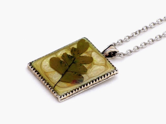 This necklace features a pendant with pressed leaves. The leaves are laid in glossy crystal resin on a platinum plated bezel. The background is handpainted with prism effects paint.