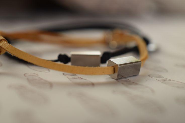 HRANOL-Vyroben z probarvené pískové a černé kůže s komponentem z chirurgické oceli ve tvaru kvádru, velikosti 1 cm zapínání pomocí zdrhovacího uzlu, s medailonkem Impronte.