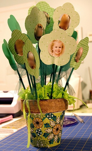 This looks a little sloppy but I like the idea of die cutting a child's face out and making a flower to stick into a centerpiece or other arrangement. Would be great for xmas or other holiday for grandparents