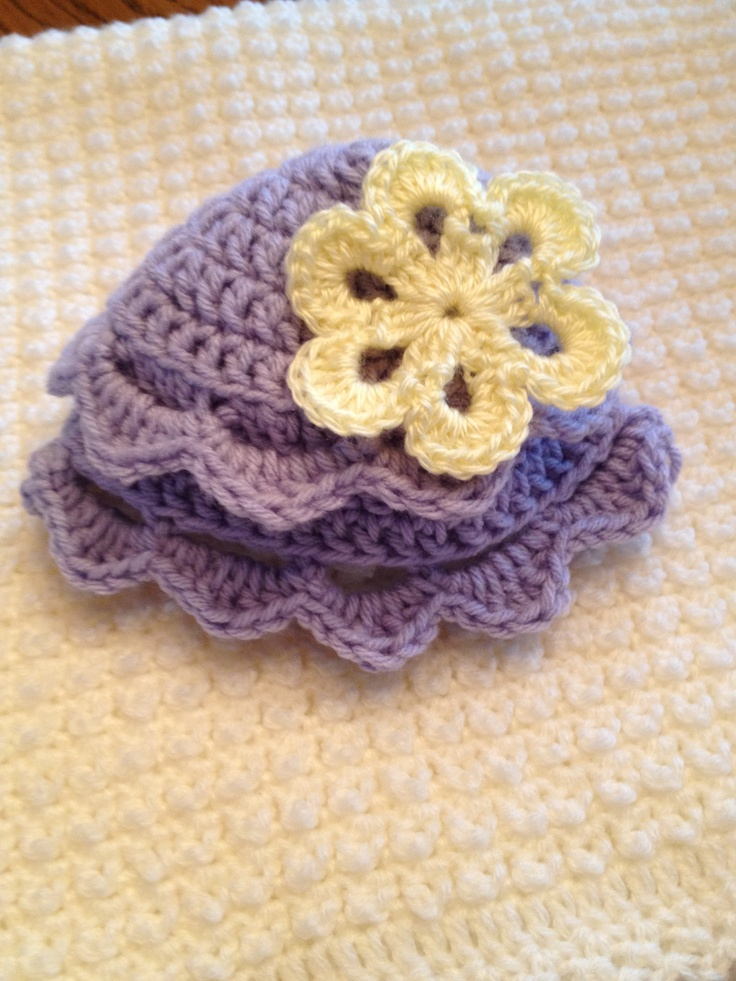 Crocheted purple with yellow flower baby cap.