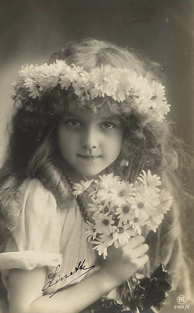 Girl with a crown and bouquet of daisies