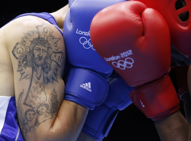 Moldova's Vasilii Belous (L) sports a tattoo as he fights against Tanzania's Selemani  Kidunda during the men's welter (69kg) Round of 32 boxing match at ExCeL venue during the London 2012