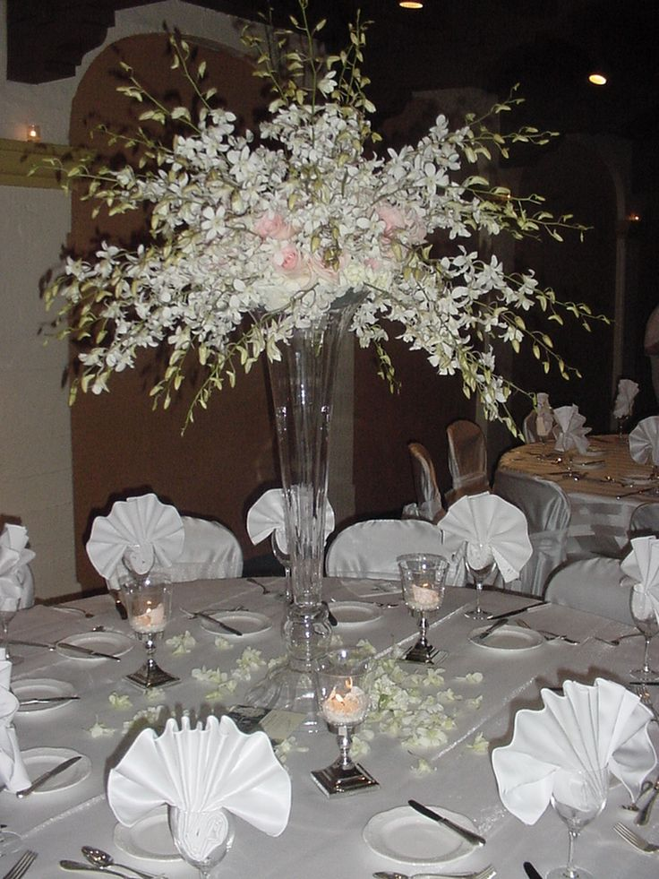 White dendrobium orchid sprays in a tall vase check on
