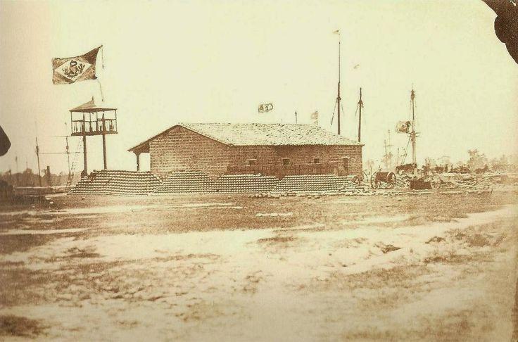 A bandeira do Brasil Imperial tremula na cidade paraguaia de Humaitá, ao fundo podemos ver mastros de navios de guerra ancorados no Rio Paraguai,1868.
