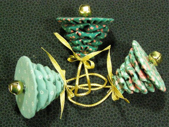 Three Christmas tree ornaments made of fabric yo yos to look like miniature Christmas trees. Each ornament consists of six yo yos, made of calico