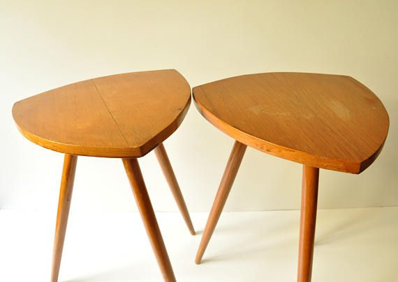 Lovely set of two midcentury modern tripod coffee tables. Perfect for bedside tables or next to an armchair as coffee tables or even for a corner as plant tables.  Both wooden, very stylish, overall in good vintage condition. They do show some discoloration on top sides as seen in photo 2 which could easily be removed if the tables are rubbed with sandpaper and polished.  Their legs can be easily unscrewed by hand so they will be shipped safely as a flat package…