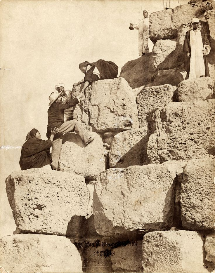 Guides help a man climb the blocks of Khufu's Pyramid in 1913 -- National Geographic