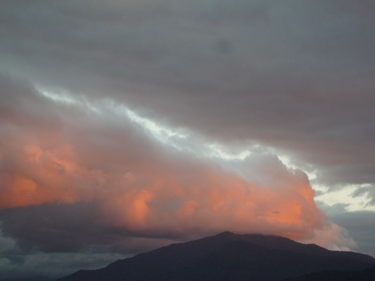 Its not a volcano! It is the sun reflecting on the clouds over the mountain forest behind Cains, Qld.