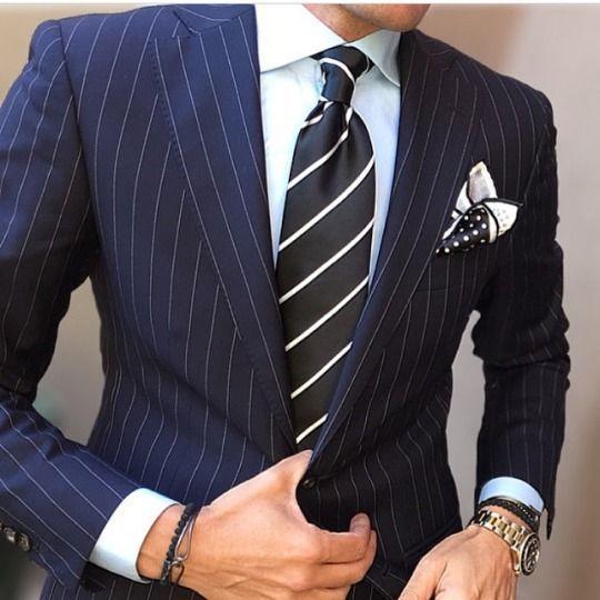 Acheter la tenue sur Lookastic: https://lookastic.fr/mode-homme/tenues/costume-chemise-de-ville-cravate/19262   — Chemise de ville blanche  — Cravate à rayures verticales noir et blanc  — Pochette de costume á pois noir et blanc  — Costume à rayures verticales bleu marine  — Bracelet noir  — Montre doré