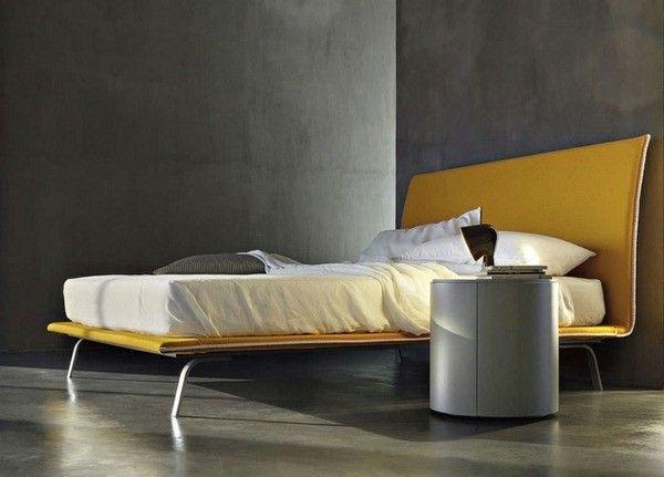 cadre de lit jambes métalliques jaunes mur de béton table ronde de nuit