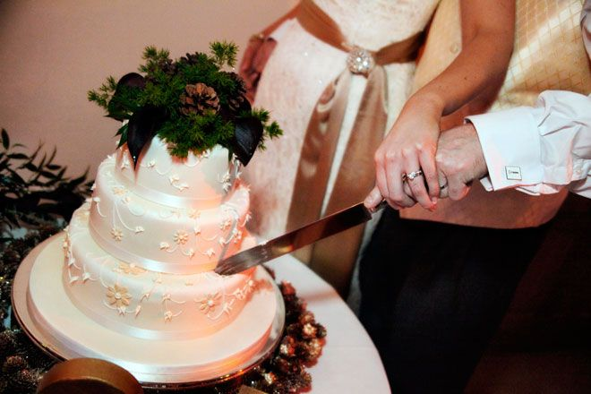 Bride and groom cutting a Christmas themed wedding cake at a Rivervale Barn | www.allabouttheimage.co.uk
