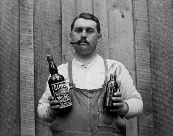 A cigar smoking man poses with a bottle of whiskey and a bottle of beer.  –Image by © DaZo Vintage Stock Photos/Images.com/Corbis