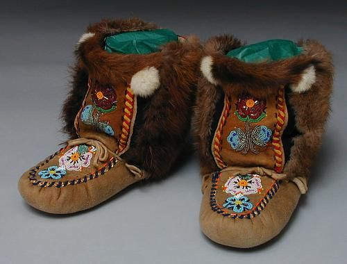 These are fabulous mukluks made by a member of the Selkirk Band in the Yukon. They are beaded on smoked moosehide and have beaver fur on the sides and some other kind of fur on the tops. See a close-up of the beadwork on the vamps and on the tops.