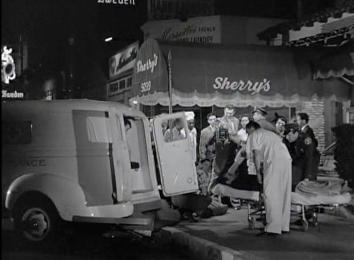 Mickey Cohen's bodyguard Neddie Herbert is loaded into an ambulance after Cohen and his entourage were ambushed by two men with shotguns outside Sherry's nightclub on the Sunset Strip, July 20, 1949.