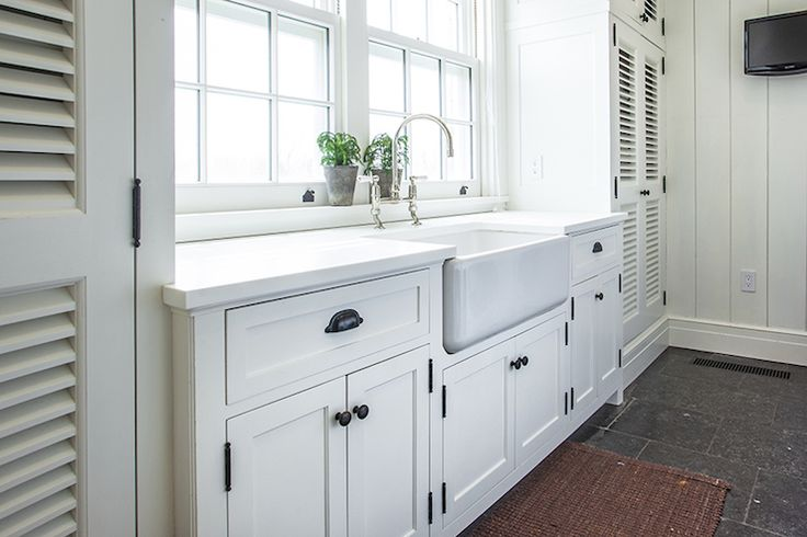 Cottage laundry room features white shaker cabinets for White bathroom cabinets with bronze hardware