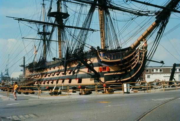 A tourist poses in front of the tall ship HMS Victory Portsmouth United Kingdom 1970
