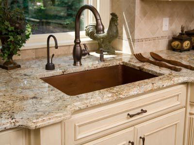 Rich copper sink contrasting with light granite over painted cabinets.  Nice.