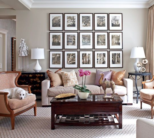 Sepia-toned landscape photos create an artistic focal point within a living room dressed in restrained shades of beige and chocolate brown. A single amethyst pillow breaks up the understated palette.  Once again, the dog claims the best seat in the house!