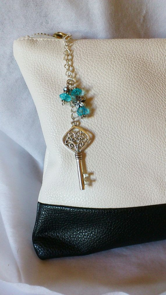 A lovely double strain purse charm. A pretty silver plated wedding key charm. There are beautiful sea blue beads and a gunmetal daisy spacers.