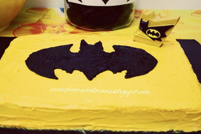 print and cut out batman logo and place on cake. trace with black icing and then fill