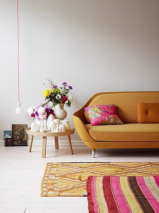 Beautiful colours, layered rugs, fabulous sofa ... low hanging light!