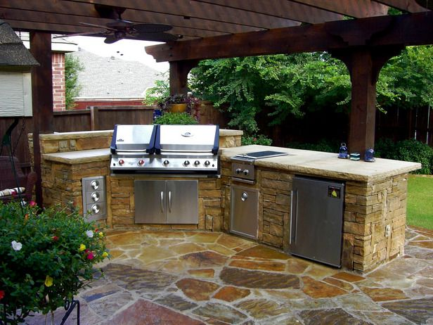 12 Amazing Outdoor Kitchens: The stacked-stone kitchen unit is topped a flat stone countertop, surrounded by stainless-steel appliances, Oklahoma flagstone patio and a rough cedar arbor. From DIYnetwork.com