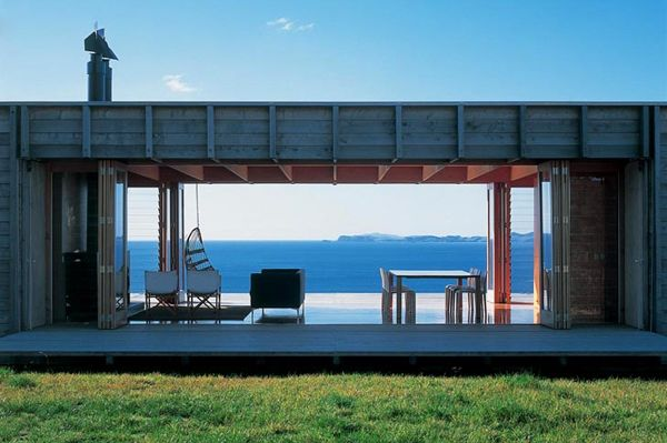 Coromandel Beach House. An open plan living space forms the majority of the house, with windows across both front and back, flowing casually onto the sand and directly down to the water. Two bedrooms are located either side of the bathroom adjacent to the kitchen. The large fireplace allows winter occupation. Concealed glass panels extend out of the walls to close off spaces as required.