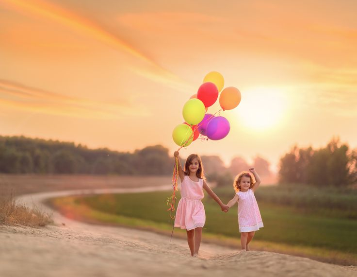 Two sisters walking up a dirt country road with older sister holding helium filled balloons and the younger sister imitating her but without any balloons.
