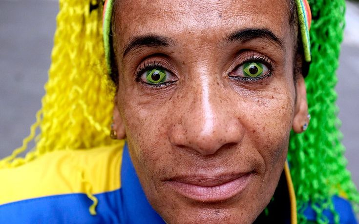 Ana Luiza, wearing contact lenses in the colours of the Brazilian national flag, poses on a street in Sao Paulo