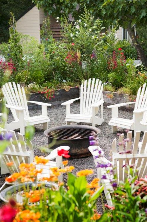 A fire pit, gravel and adirondack chairs on north side of the house.