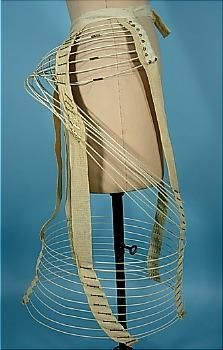 """1872-  crinolette jaula de alambre o Hoop bullía de accesorios de latón """". Crinolettes marcó el punto medio entre la jaula crinolina y el bullicio de la moda entre 1867 y mediados de la década de 1870, se compone a menudo de aros de media con bucles adicionales de acero en la parte superior para dar más apoyo. Durante la década de 1870 el movimiento se convirtió en una prenda separada """".  material: cinta de sarga y alambre"""