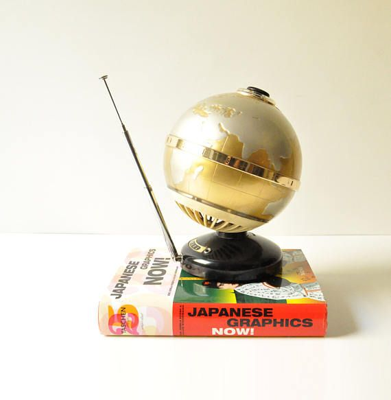This fabulous unusual and very rare golden globe radio was manufactured in Japan in 1965 by Marc company. In perfect working condition.  On the metal equatorial ring it has the molded inscription All Transistor. The speaker is facing down and the sound comes out from the vents of the white grill located in the south pole of the globe.*  The controls are visible on the photos: the black knob for the power switch / volume control is on the north pole, the sliding tuner control extends from...