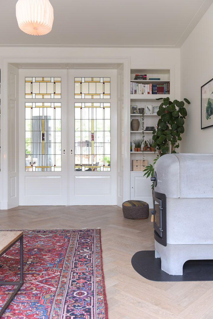 Totale verbouwing van jaren 30 villa in Alkmaar. De ruime woonkamer wordt, met een klassieke kamer en suite met half open kasten en glas in lood deuren, gescheiden van de leefkeuken. Op de vloer een eiken visgraad vloer met een stoere houthaard van Weltevree. #weltevree #stonestove #kamerensuite www.pieterdeboer.com