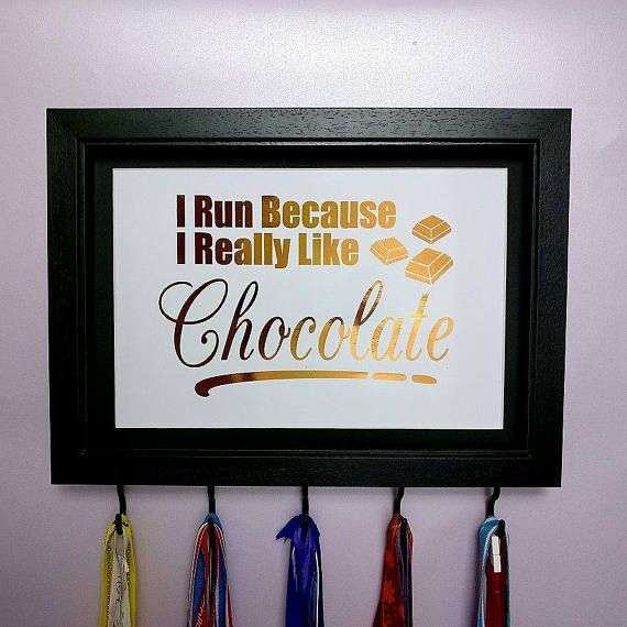 I Run Because I Really Like Chocolate Medal Hanger Frame Colour Options  Medal Hanger with 5 matching hooks.  These unique medal hangers are a great gift or treat for yourself. Have you got medals hanging on doors, hidden away in cupboards or stored in a box? Get them out and show them off!  These medal hanger frames are customisable so you can choose which colour frame you would like and your favourite foil colour.  Great gift for chocolate lovers